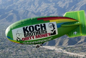 """The Greenpeace Airship A.E. Bates flies over the location of oil billionaires David and Charles Koch's latest secret political strategy meeting, with a banner reading """"Koch Brothers: Dirty Money."""" The aerial message is directed to arriving attendees of the meeting and highlights the Koch Brothers' ongoing use of their vast oil profits to push a polluter agenda through campaign contributions, lobbying, and funding fronts groups and think tanks."""